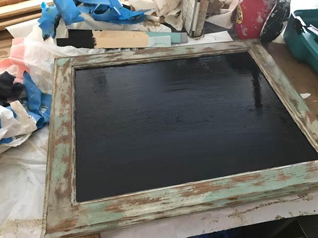 Applied and waiting for the Rustoleum chalkboard paint to dry in the center of the cabinet